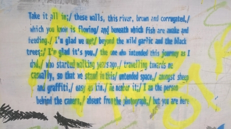 Graffiti of poem in blue writing on white background