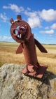 Metal owl sculpture on dry stone wall with corn field and blue sky behind