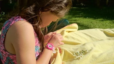 Girl making daisy chains with blanket