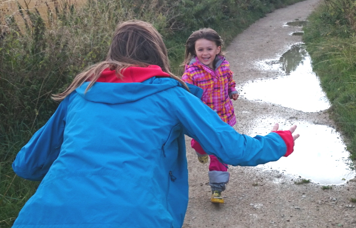 Child girl running towards woman mother past puddles with outstrectched arms and smile