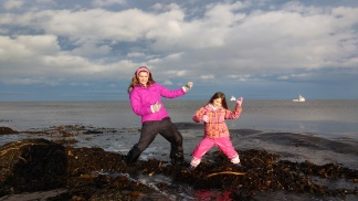 Woman and child girl mother and daughter doing air guitar on seaweed at beach