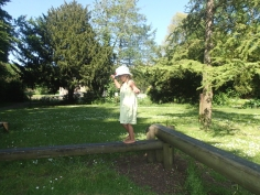 Barefoot girl in sundress and sunhat on outdoor balance beam