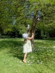 Barefoot girl in sunhat on grass reaching up to branches of a tree