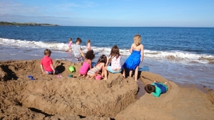 children-sitting-on-large-sand-castle-on-beach-hogwarts