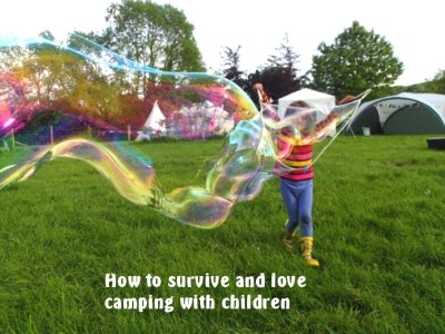 girl-blowing-giant-bubbles-in-field-with-tent-and-tipi-behind-and-words.jpg