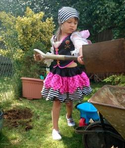 girl-in-pirate-costume-throwing-soil-into-wheelbarrow-with-spade