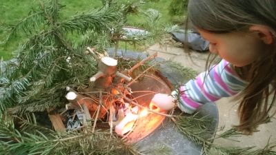 girl-lighting-evergreen-branches-in-firepit
