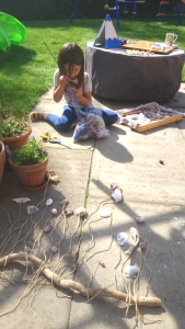 girl-on-ground-in-garden-with-shells-and-bag-of-wool-creating-artwork