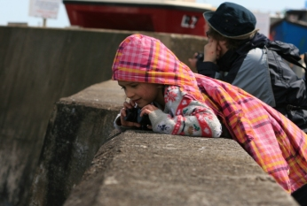 girl-with-binoculars-leaning-over-harbour-wall