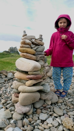 girl-with-cairn-of-stones-with-caastle-in-background-holy-island