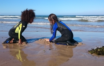 girls-in-wetsuits-kneeling-on-beach