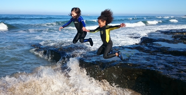 girls-in-wetsuits-leaping-from-rocks-into-foaming-sea