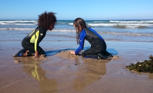 girls-in-wetsuits-on-beach-with-mound-of-sand-and-pile-of-seaweed-in-front-of-surf