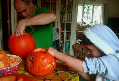 mage of man-and-girl-carving-pumpkins-at-a-table-with-skeleton-in-background