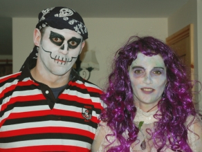 mage of man-in-pirate-skeleton-costume-and-woman-in-purple-wig-halloween-costume