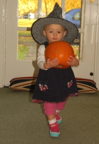 Image of toddler-in-witches-hat-carrying-pumpkin