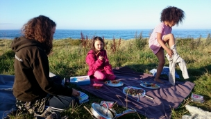 two-girls-and-woman-having-meal-on-rug-overlooking-the-sea