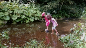 two-girls-crossing-stream-on-steping-stones