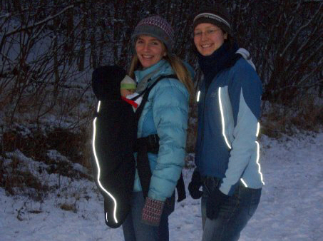 Image of two-women-outdoors-in-snow-wearing-outdoor-gear-and-baby-in-an-inward-facing-carrier