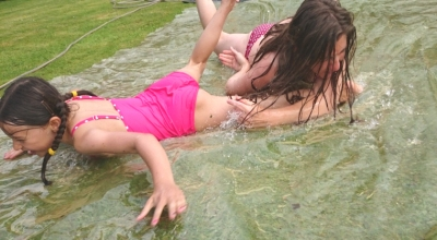 woman-and-girl-on-water-slide-in-garden