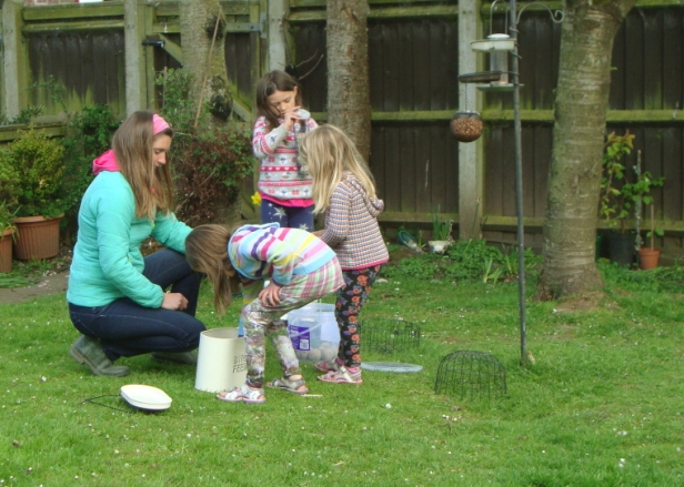 woman-and-girls-filling-bird-feeders-in-garden