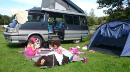 woman-and-two-girls-on-rug-outside-tent-and-camper-van