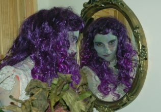 mage of woman-looking-in-mirror-with-purple-wig-halloween-fancy-dress