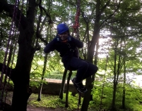 boy-giving-thumbs-up-in-climbing-harness-in-tree