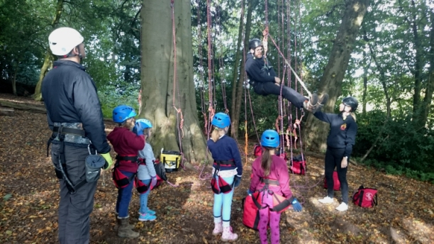children-with-climbing-ropes-being-given-demo-at-bottom-of-tree