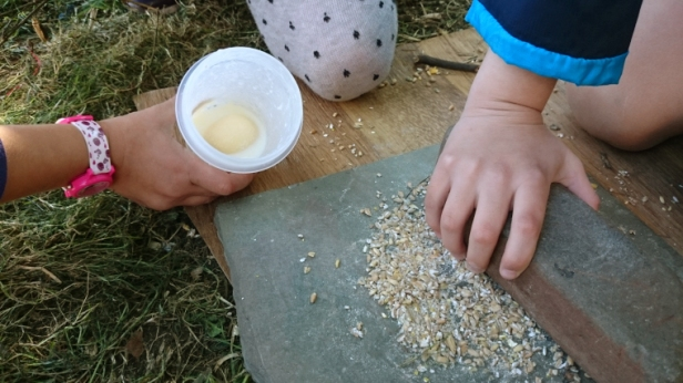 childrens-hands-with-seeds-on-stone-and-butter-in-pot