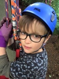 close-up-of-boy-in-climbing-gear-in-tree