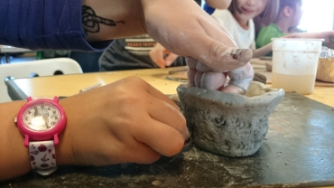 close-up-of-childs-hands-decorating-clay-pot-with-pine-cone-patterns