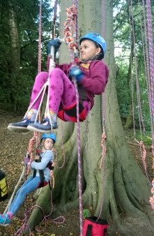 girl-in-squat-position-in-climbing-harness-on-ropes