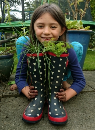 girl-squatting-behind-pair-of-wellies-planted-with-herbs
