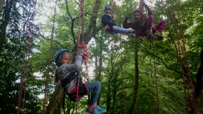 three-girls-in-climbing-harnesses-in-tree