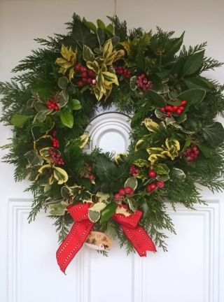 evergreen-christmas-wreath-with-berries-and-red-ribbon-hanging-on-white-door