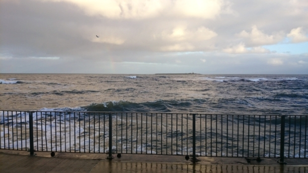 brooding-sea-with-pale-rainbow-on-horizon-next-to-island-railings-in-foreground
