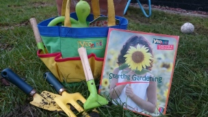 Children's pocketed bag with mini gardening tools and book on grass