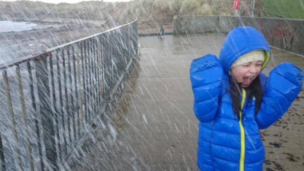 girl-in-blue-coat-laughing-at-being-soaked-by-giant-wave-over-sea-wall-railings