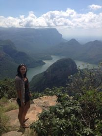 woman standing on rock with stunning lake and mountain valley view