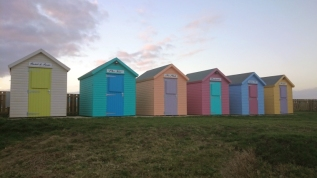 pastel-coloured-row-of-beach-huts-with-grass-in-front-at-sunset
