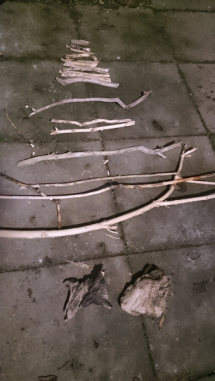 pieces-of-driftwood-sticks-layed-on-ground-in-pyramid-shape