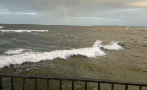 rough-grey-sea-with-small-island-and-faint-rainbow-at-horixon