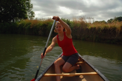 woman-in-kayak-on-river-with-bank-in-background