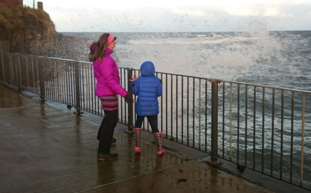 woman-in-purple-coat-and-child-in-blue-coat-being-splashed-by-waves-near-railings-at-the-sea