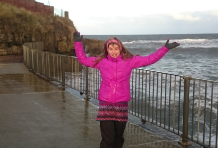 woman-with-arms-in-air-in-wet-purple-coat-near-railings-at-the-sea