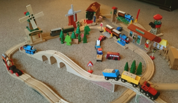 wooden-train-set-laid-out-with-bridges-buildings-trains-vehicles-and-people