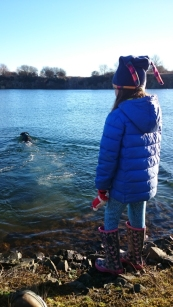 girl-in-blue-coat-by-quarry-lake-with-black-dog-swimming
