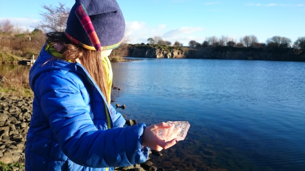 girl-in-blue-coat-and-woolly-hat-skimming-a-piece-of-ice-on-quarry-lake