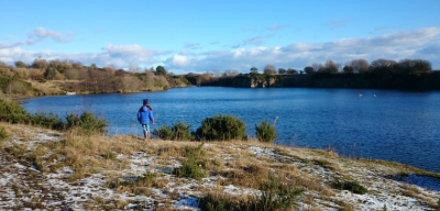 girl-in-blue-coat-in-front-of-quarry-lake-on-sunny-day-with-snow-in-foreground
